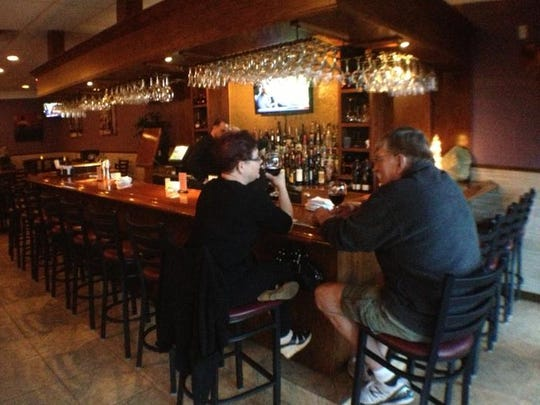 Patrons sit at the bar at Courtney's Continental Cuisine