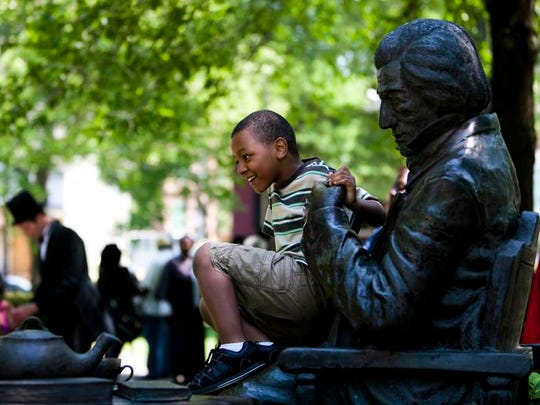 Khigee Calhoun interacts with the statue of Frederick Douglass during the 2013 Juneteenth  Historical Commemoration.