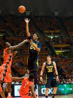 Michigan Wolverines guard Aubrey Dawkins (24) shoots defended by Illinois Fighting Illini center Nnanna Egwu (32) at State Farm Center.