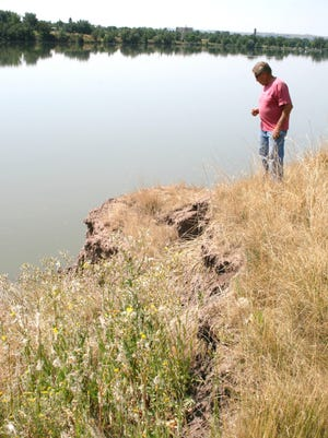 River's Edge Trail planner Doug Wicks explored a crack in the north bank of the Missouri River near West Bank Park in August 2014 where erosion has caused the bank to slough off into the river.