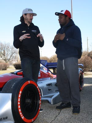 IndyCar driver J.R. Hildebrand talks with Detroit Central senior Desmond Riggins about the various types of tires used in racing.