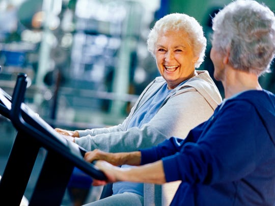 Two senior women exercising in a health club