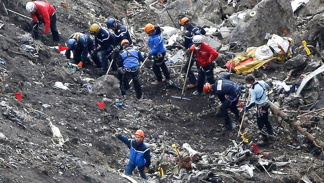 Rescue workers look over debris from the Germanwings jet at the crash site near Seyne-les-Alpes, France, on March 26.