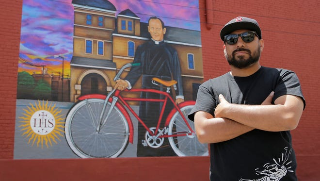 """In this 2015 photo, El Paso muralist Jesus """"Cimi"""" Alvarado stands next to his mural in honor of Father Rahm at the intersection of Father Rahm and South El Paso Street."""