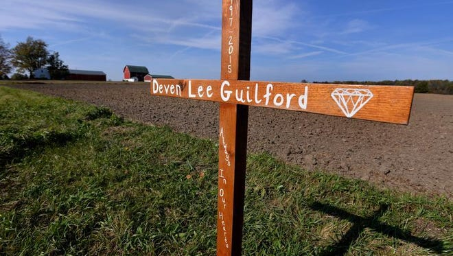 A small wooden cross on M-43 between Grand Ledge and Mulliken stands near a farm field Monday near the area where Deven Guilford, 17, died after a traffic stop and confrontation with an Eaton County Sheriff's sergeant.