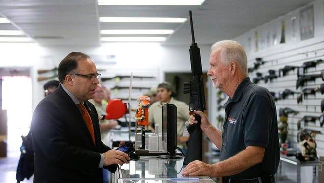 Sales associate Mike Conway shows Paul Angulo a  rifle at Bullseye Sport gun shop in Riverside, Calif. Gun sales in the region have skyrocketed even before the  shooting in San Bernardino.