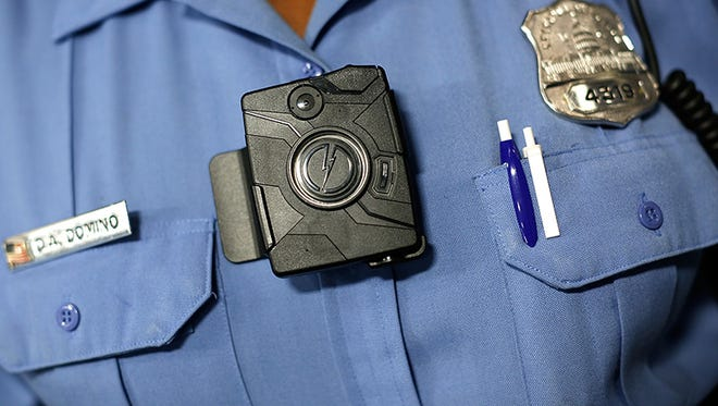"A Washington DC Metropolitan Police Officer wears one of the new ""body-worn cameras"" that the city's officers will begin using during a press conference."