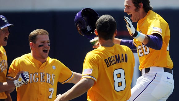 LSU's Conner Hale (20) is congratulated by teammates Andrew Stevenson, left, Sean McMullen (7) and Alex Bregman (8) following his eighth-inning solo home run against Ole Miss Saturday. LSU won 2-0.