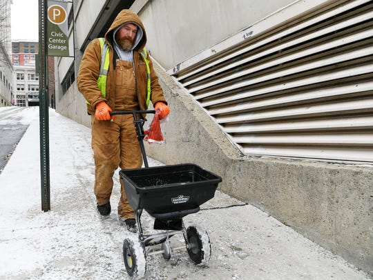 Josh Heath salts the sidewalk on W Walnut Street in