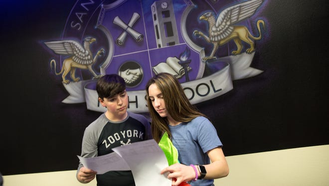 Students Carson Evans and Valeria Bandy look over their class schedule for the 2017 school year on Dec. 15 at San Juan College High School in Farmington.