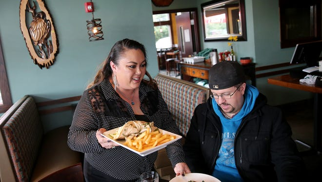 Kafe Neo in Kingston general manager Heather Mattox delivers lunch to Kyle Rowland of Poulsbo.