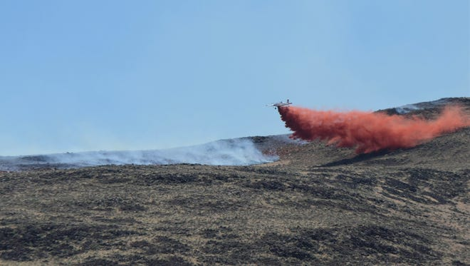 A single-engine airtanker drops retardant Monday, June 4, 2018 on a ridge line above a small neighborhood just south of U.S. 50 during the Chaves Fire.