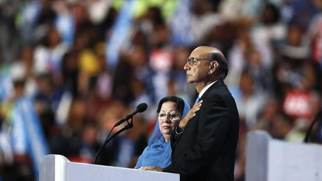 Khizr Khan, father of fallen US Army Capt. Humayun S. M. Khan, speaks while his wife Ghazala Khan looks on, during the final day of the Democratic National Convention in Philadelphia, Thursday, July 28, 2016. (AP Photo/Paul Sancya)