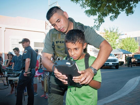Jett Loe — Sun-News   Christian Griffin, 8,  gets instruction on steering a surveillance robot from LCPD Officer Justin Ramirez at the National Night Out event.