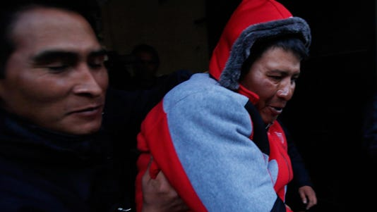 Javier Cusi Aduviri is escorted by Bolivian police officers at the police station in El Alto.