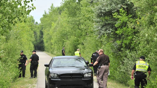 Police comb a wooded area where a girl's body was found.