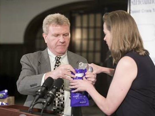 Martin Rosenzweig, chief medical officer at Optum Behavioral Health, demonstrates the opioid disposal kits with Allison Davenport, CEO, UnitedHealthcare Community Plan of Pennsylvania.