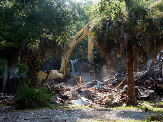 Two houses and a former business are demolished June 29 to make room for a new Taco Bell restaurant in East Hill.