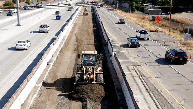 In file photo, vehicles pass a highway construction site on Interstate 80 in Sacramento, Calif. A plan to revitalize America's aging infrastructure put forward by two President Donald Trump administration economic advisers relies on a transportation financing scheme that hasn't been tried before and comes with significant risks.