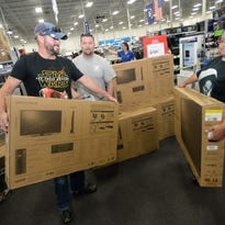 Hope Hollins (right) Nick Lawson (center) and Patrick Dault each grab a flat screen TV while shopping at Best Buy Thursday evening during the black friday sales.