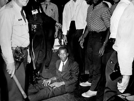 John Lewis, member of the Nashville Christian Leadership Council, sits in the street May 13, 1963, in protest of Nashville police arresting Lamar Richardson, a Fisk University student. The group was having a sit-in demonstration in front of the B & W Cafeteria.