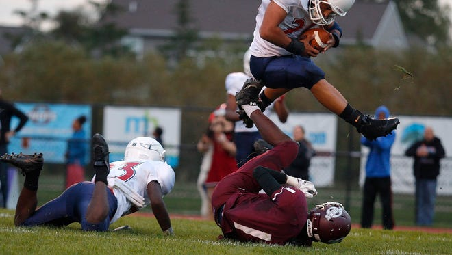 Everett's Diego Martin, top, pulls in the ball over Okemos receiver Chaz Richardson but it had already hit the ground for an incomplete pass after being broken up by Everett's Leslie Buck, left, Friday, Sept. 11, 2015, in Okemos. Everett won 33-24.
