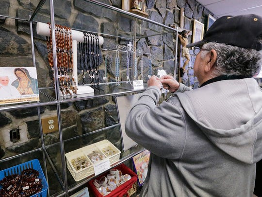 A shopper looked at some of the papal items for sale Wednesday at The Madonna Shop.