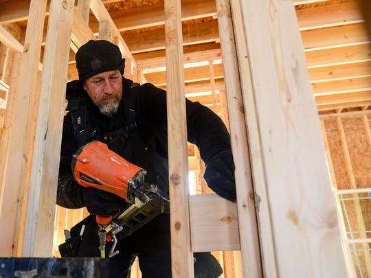 Matt Withem, of Skidoo Construction, puts the final touches on the framing of an interior wall at a house being built on Wildflower Drive in Delhi Township on Tuesday, Dec. 13, 2016. New housing starts have doubled since the recession, steadily growing thanks to an improving economy, low interest rates and the option to build exactly to the customer's needs.