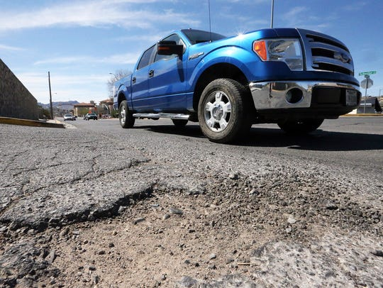 Potholes and cracks along Schuster Avenue at the intersection