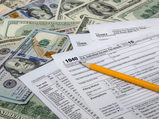 Tax forms and a pencil on top of a spread-out pile of $100 bills.