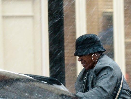Pedestrians walk through the rain in downtown Montgomery,