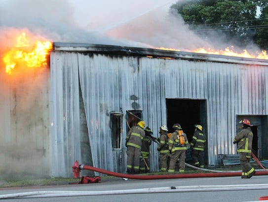 Firefighters work to control a fire at a building on
