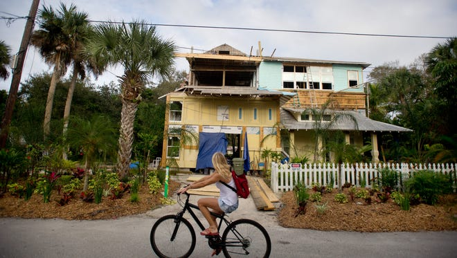 A bicyclist rides past a construction site at 823 St. Lucie Crescent on Jan. 15, 2015 in Stuart.
