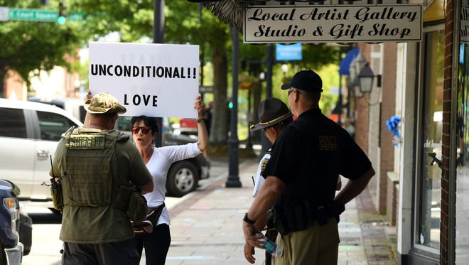 A member of the sheriffs department confronts a woman with a sign after she was burning sage in Downtown Newnan in anticipation of first major face off between neo-Nazis, white supremacist groups and anti-fascist forces since last year's deadly clashes in Charlottesville, Va.