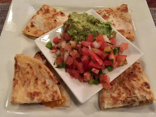 Mounds of guacamole and pico de gallo accompany grilled chicken quesadilla wedges at Rapscallion Seafood House & Bar.