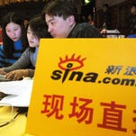 Chinese youths work on a computer, using Chinese net portal Sina.com, for a live broadcast of a media event on Jan. 8, 2003.