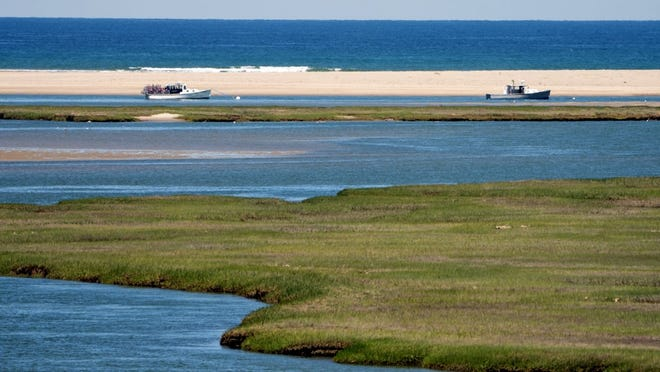 Fishing boats anchor near the inlet at Nauset Marsh, where low tide prevents access due to the silted-in condition of the channel.