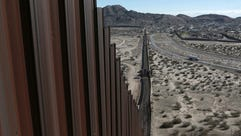 A truck driving near the Mexico-U.S. border fence,
