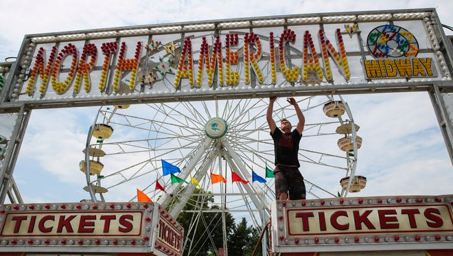 """A Midway employee works on the ticket area and entrance at the Kentucky State Fair during set-up Wednesday. """"It's a once a year thing for families, it's memories for a lifetime,"""" director of guest services Patti Power said as she described the magic of the fair. """"They'll always remember it."""" Aug. 19, 2015"""