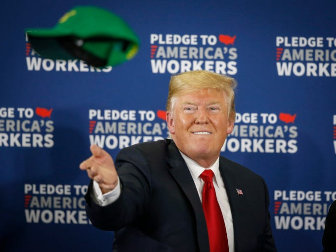 "President Donald Trump tosses a green ""Make Farmers"