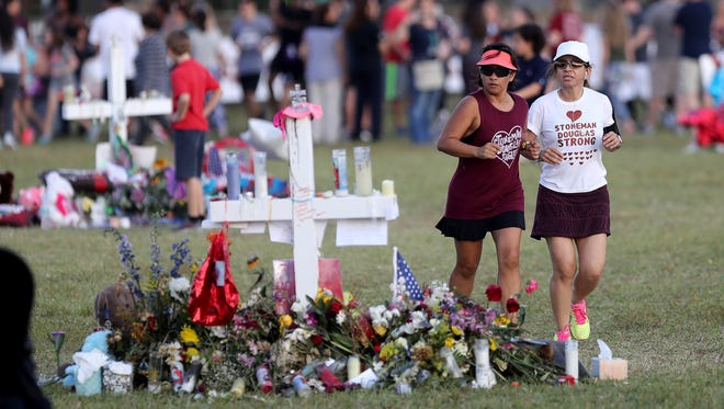 Runners run past the memorial for the victims of last week's school shooting at Pine Trails Park in Parkland, Fla., on Feb. 21, 2018.