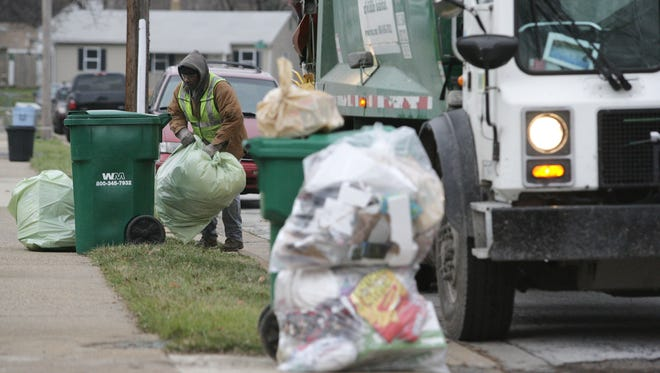 A trash collector with Waste Management picks up garbage in the Overview Garden neighborhood on Dec. 26, 2007.