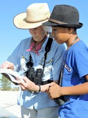 Patricia Taber helps Angel Zeferino identify a bird at the Deming water treatment plant.