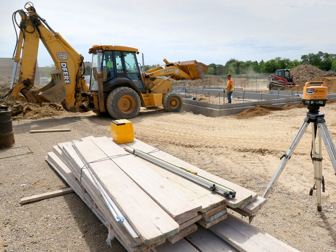 Contractors backfill the foundation for a concessions