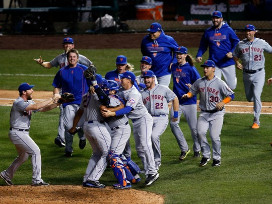 The New York Mets celebrate after Game 4 of the National League baseball championship series against the Chicago Cubs Wednesday, Oct. 21, 2015, in Chicago. The Mets won 8-3 to advance to the World Series. (AP Photo/Charles Rex Arbogast)