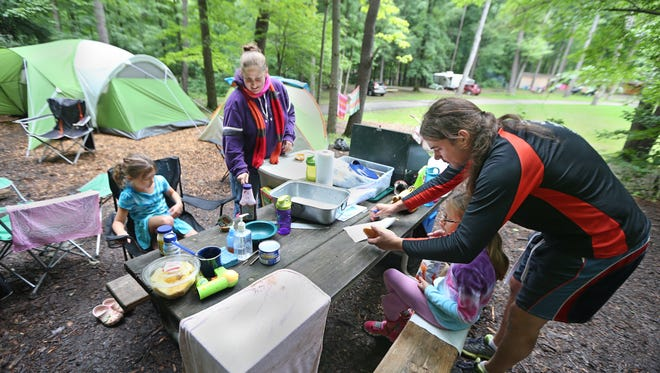 John and Angelica Butte, of Baltimore, serve up a hot grilled lunch to their daughters, Isabella, 5, left, and Samarra, 8, at their campsite near the Upper Park Entrance at Stony Brook State Park in Dansville last summer. Camping is one of the most popular activities  at the park.