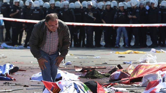 A man stands over the body of a victim at the scene of an explosion in Ankara, Turkey, Saturday, Oct. 10, 2015.