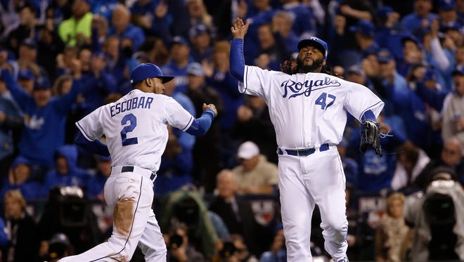 Kansas City Royals pitcher Johnny Cueto (47) celebrates with Alcides Escobar after a ground ended the seventh inning of Game 2 of the Major League Baseball World Series against the New York Mets Wednesday, Oct. 28, 2015, in Kansas City, Mo.