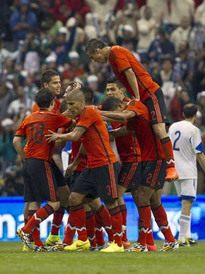 Mexico soccer team players celebrate after scoring against Israel during a friendly match in Mexico City.