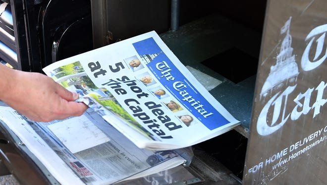 A reporter buys a Capital Gazette newspaper on June 29, 2018, in Annapolis, Maryland.